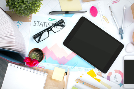 business supplies: Top view and closeup of messy office desktop with blank tablet, cellphone, glasses, decorative plants, business report, open book, colorful supplies and other items. Mock up