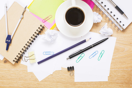 Top view of creative messy wooden desktop with coffee cup and various stationery items Stock Photo