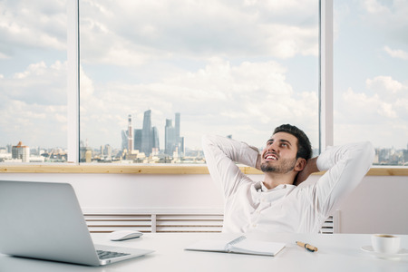 hands on head: Young caucasian businessperson relaxing in modern bright office room with city view Stock Photo