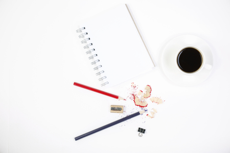 coloured: Top view of white desktop with pencils, sharpener, sawdust, small peg, spiral notepad and coffee cup