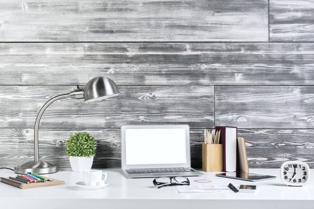 home office desk: Front view of creative designer desktop with blank laptop, table lamp, tablet, coffee cup, decorative plants, clock. Mock up Stock Photo