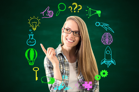 Confident smiling young woman pointing at round business sketch on chalkboard background. Success concept