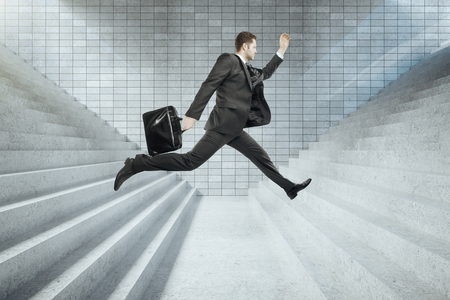 hopping: Success concept with businessman in suit jumping from one concrete staircase to another
