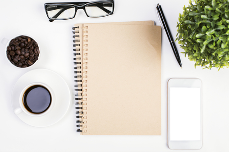 legal pad: Top view of white office desktop with blank spiral notepad, empty white smartphone screen, coffee, glasses, plant and other items. Close up, Mock up