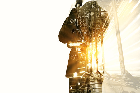 Back view of thoughtful businessman on abstract city and construction background with sunlight and copyspace. Double exposure