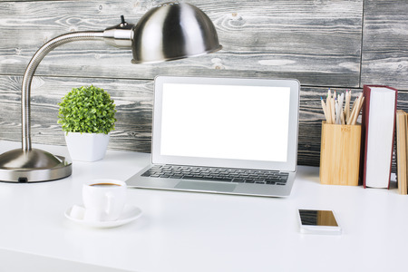 desktop computer: Closeup of creative designer workplace with blank white laptop screen, smartphone, coffee cup, table lamp, plant, books and pencils on wooden wall background. Mock up