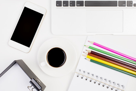 stationery items: Top view of white office table with blank smartphone, coffee cup, laptop keyabord and stationery items. Mock up