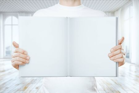 man holding book: Young man holding empty open book in interior. Mock up, 3D Rendering Stock Photo