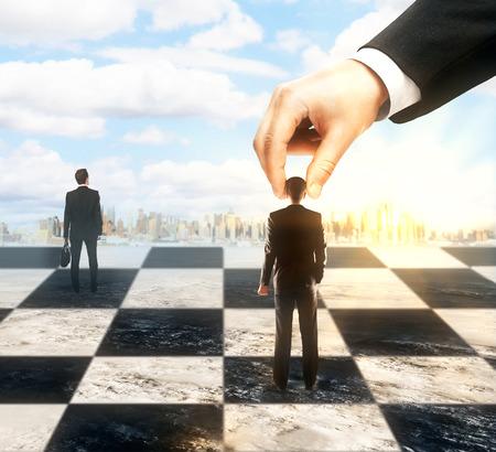 planeación estrategica: La planificación estratégica y el concepto de control con la mano empresarios en movimiento en el tablero de ajedrez. Ciudad y el cielo de fondo Foto de archivo