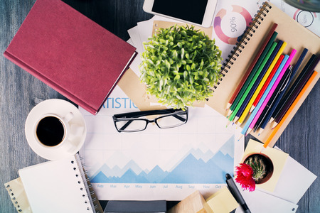 stationery items: Top view of messy office desktop with closed hardcover book, coffee cup, glasses, business report, plants and various stationery items Stock Photo