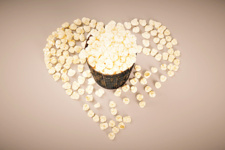 scattered in heart shaped: Movie lovers concept with film strip popcorn cup on light background. Top view, 3D Rendering Stock Photo