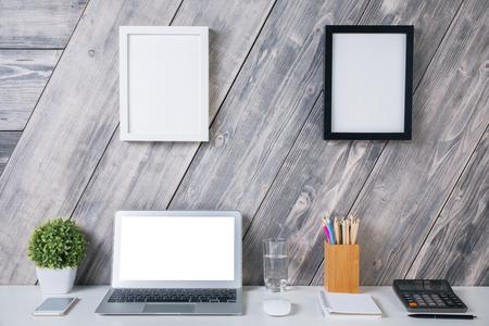 articulos oficina: el lugar de trabajo de diseño creativo con la computadora portátil en blanco blanca, planta, teléfono inteligente, el vaso de agua, calculadora, artículos de papelería y dos marcos de cuadros que cuelga sobre el fondo de madera. Bosquejo