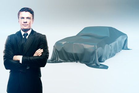 Handsome confident businessman and car covered with grey cloth on light background Stock Photo