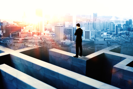 businessman thinking: Businessman on top of concrete maze wall thinking on city background with sunlight