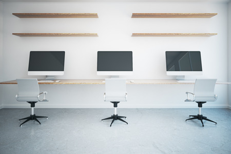 three shelves: Coworking office interior with three blank computer monitors, table, chairs and shelves on concrete background. Mock up, 3D Rendering