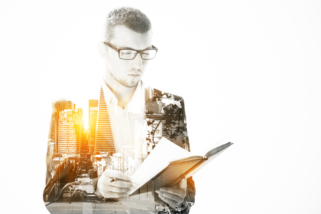 Young businessman in glasses reading book on city background with sunlight. Double exposure.