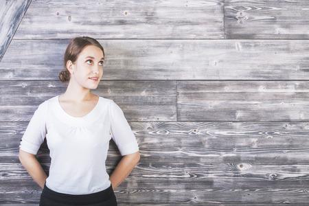 gefesselt: Portrait der schönen jungen Frau, die gegen texturierte Holzwand mit Exemplar
