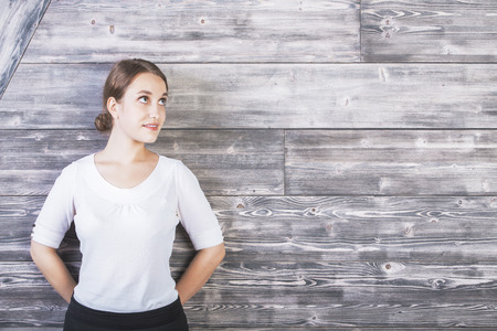 woman tied: Portrait of beautiful young woman standing against textured wooden wall with copyspace