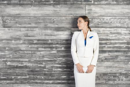 white suit: Thoughtful business woman in white suit standing against dark wooden wall with copy space