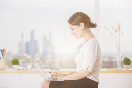 Side view of attractive smiling businesswoman using laptop in modern office interior with blurry city view