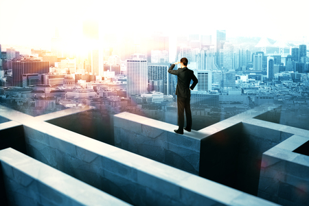success man: Businessperson on top of concrete maze wall looking into the distance on city background with sunlight
