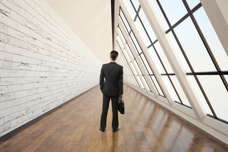businessman walking: Businessman walking in clean corridor interior with dark wooden floor, light wall, concrete ceiling and panoramic window. 3D Rendering
