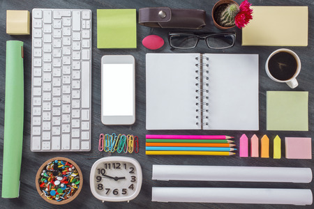 organized office: Top view of wooden office desktop with  blank white smartphone, keyboard, clock, notepad, coffee cup and other items organized in a neat and creative manner. Mock up Stock Photo