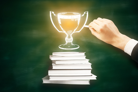 Leadership concept with businessman hand drawing abstract illuminated winners cup above book stack on chalkboard background