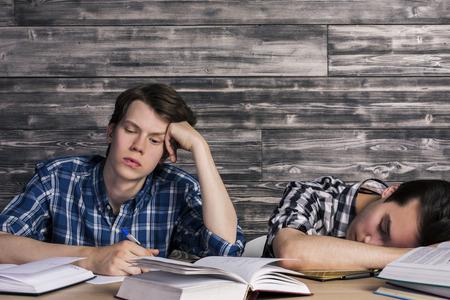 libros abiertos: Dos jóvenes estudiantes cansados ??de estudiar en la mesa de madera con muchos libros abiertos. pared de madera de textura de fondo