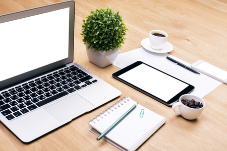 coffee coffee plant: Closeup of creative designer workplace with blank white laptop, decorative plant, spiral notepad, coffee cups, tablet, smartphone and other items. Mock up