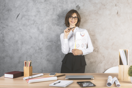oficina desordenada: Happy businesswoman with business report standing at messy office desktop on concrete wall background