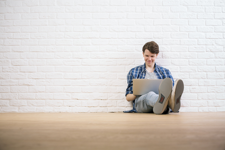 man sit: Casual guy in interior with wite brick wall sitting on wooden floor with laptop
