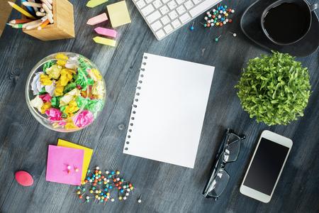Draufsicht auf kreative unordentlichen Desktop mit bunten Stiften, dekorative Schale, leere Blatt Papier, Handy, Pflanze, Kaffeetasse, Tastatur und Zubehör. Attrappe, Lehrmodell, Simulation