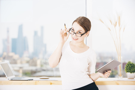 view of an elegant office: Portrait of young attractive businesswoman with digital tablet and pen in hands standing in modern office with blurry city view