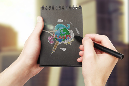 globe terrestre dessin: Male hands drawing colorful travel sketch in black spiral notepad on blurry background. Traveling concept Banque d'images