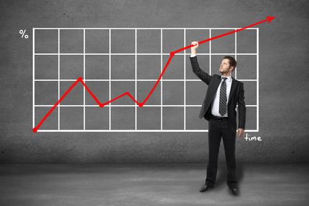 incremento: Hombre de negocios joven en el juego que sostiene resumen gráfico de flecha en el cuarto de concreto
