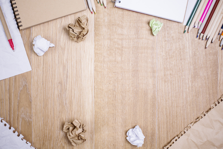 ball pens stationery: Top view of messy wooden desktop with variety of supplies and crumpled paper balls. Mock up Foto de archivo