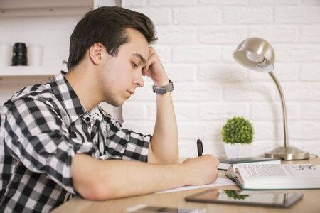 Side view of young man studying at wooden desk with open book, tablet, lamp, plant and other items on white brick wall background Stock Photo