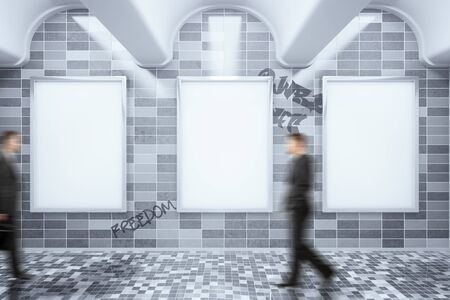 ad board: Metro station with empty ad posters hanging on dark grey tile wall with graffiti writings and blurry businessmen walking by. Mock up, 3D Rendering Stock Photo