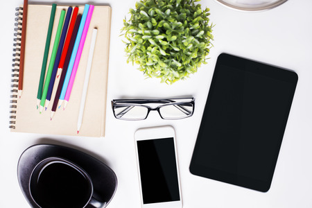 stationery items: Top view of light office desktop with blank tablet, mobile phone, cofee cup, glasses, plant and stationery items. Mock up Stock Photo