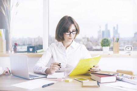 oficina desordenada: atractivo de negocios haciendo el papeleo en la oficina de escritorio desordenado con ordenador port�til, suministros y otros art�culos