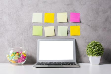 Creative hipster werkplek met lege witte laptop computer, decoratief glas kom, planten en kleurrijke stickers op de betonnen muur achtergrond. Vooraanzicht, Close-up, Mock up