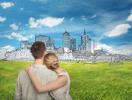 Young caucasian couple looking at cityscape sketch. Green grass and sky in the background