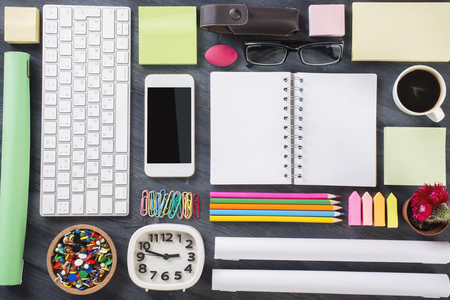 organized office: Top view of wooden office table with blank cellphone, keyboard, clock, notepad, coffee cup and other items organized in a neat and creative manner. Mock up Stock Photo