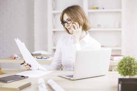 Businesswoman on phone doing paperwork in modern bright office Stock Photo