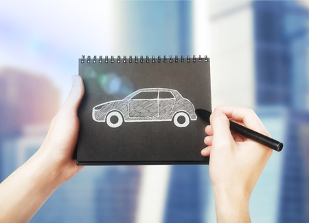motor car: Male hands drawing car sketch in black spiral notepad on blurry background