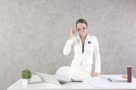 woman business suit: Confident woman standing at office desk with laptop, paperwork, smartphone, book and other items