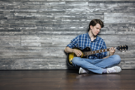 Casually dressed young man sitting on floor and playing the guitar. Textured wooden wall with copy space in the background