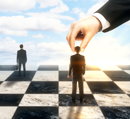Strategic planning and control concept with hand moving business people on chessboard.