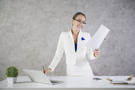 Woman with business report in hand standing at white office desk with laptop, plant, smartphone and other items. Stock Photo